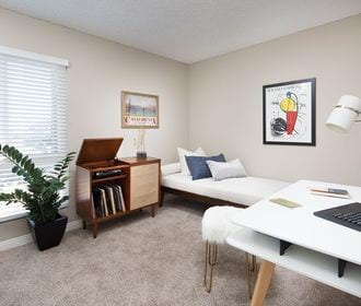 Second bedroom or office with office furniture, cot, record player, and large window.