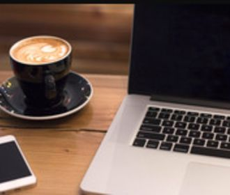 Closeup image of a computer and coffee cup sitting on a wood table.