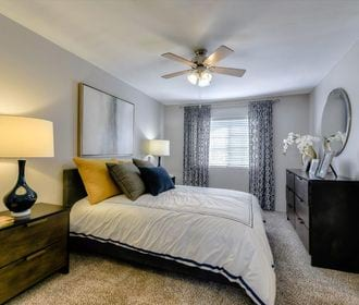 Carpeted bedroom with ceiling fan and window.