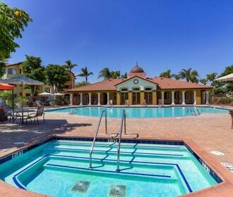 Spa with view to resort-style pool area, picnic tables, lounge seating, and gas grills.