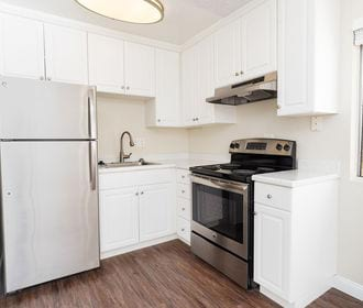 Vinyl floored kitchen with white shaker cabinets and stainless steel appliances.