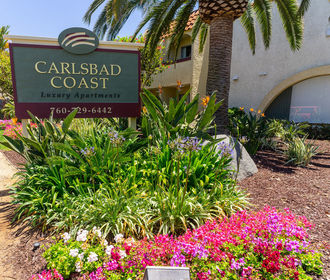 Carlsbad Coast monument sign with festive landscaping.