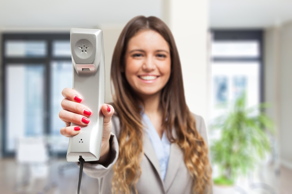 Prana Apartment Homes - Lifestyle filler image of an individual holding a phone and smiling.