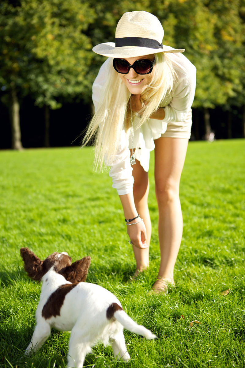 Image of an individual with a dog, standing in some grass.
