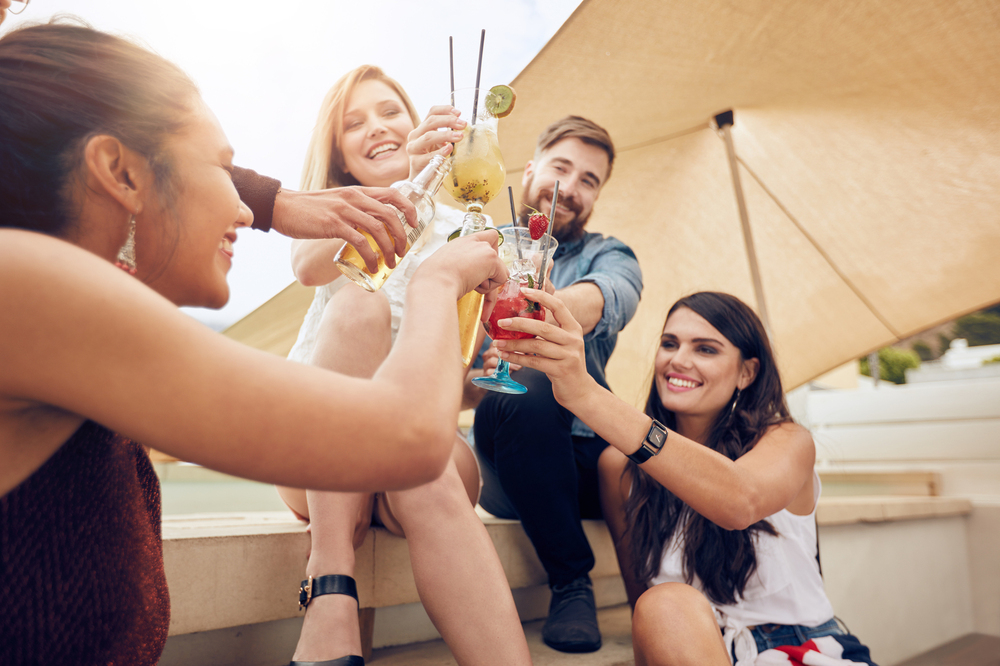 Image of four individuals enjoying beverages together outside.