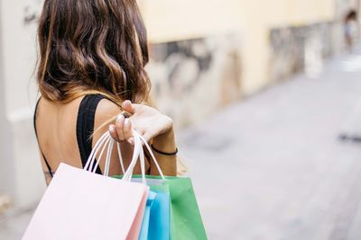 Stock image of a woman facing away from camera and holding shopping bags.