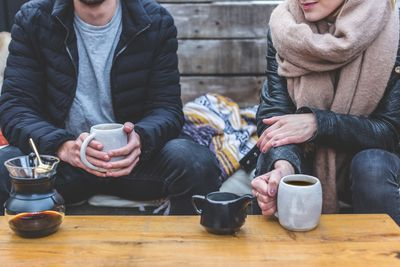 Stock image of two people sitting down having coffee.