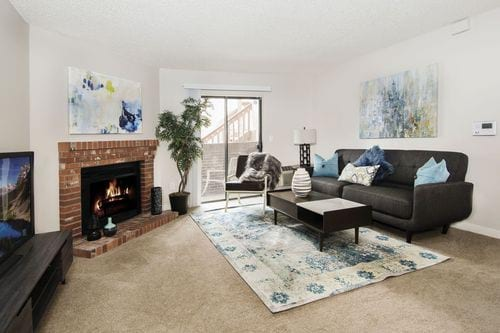 Avery Belmar - Image of the model apartment living area with a couch, table, cozy fire place, and television.