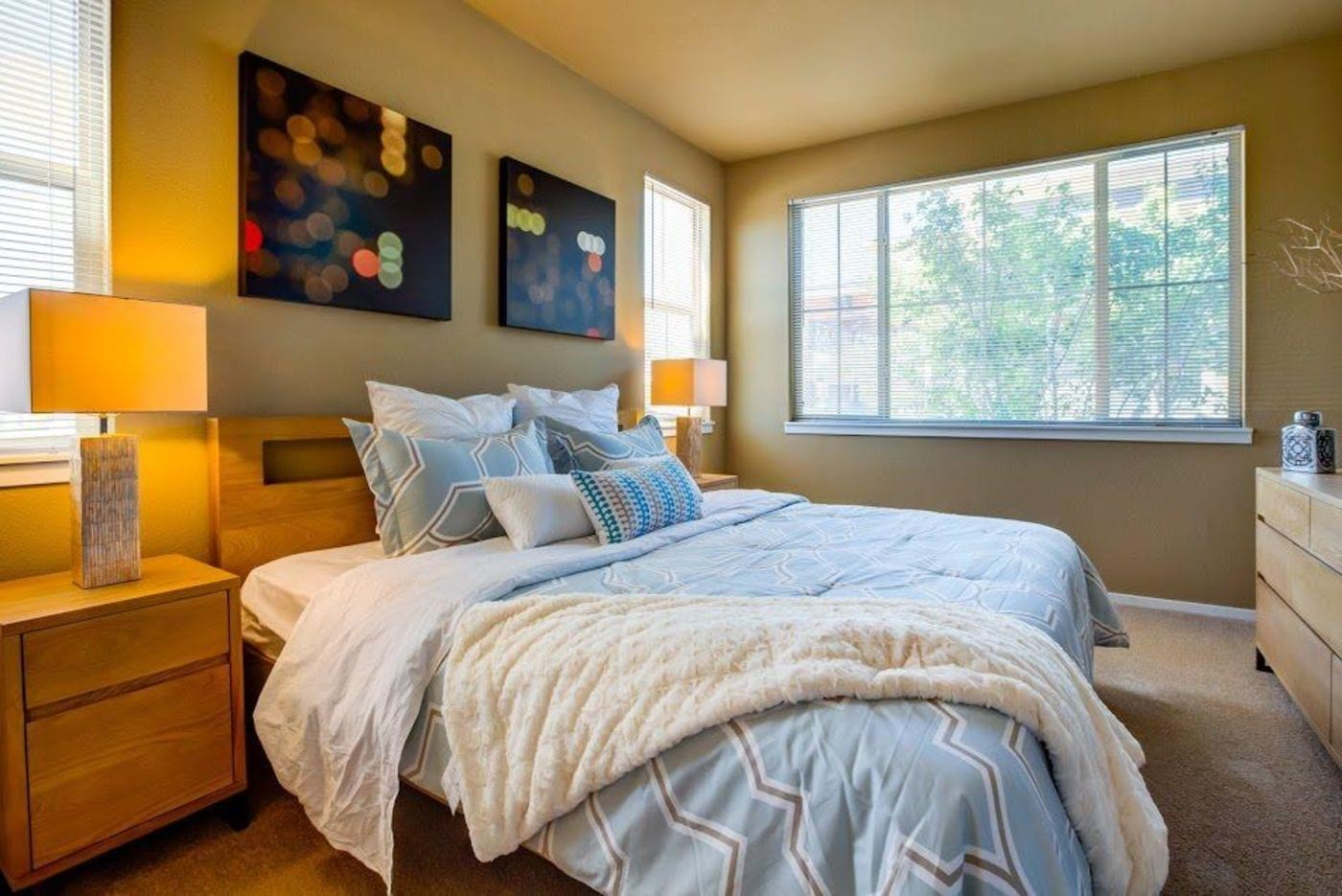 Prana Apartment Homes - Image of the model apartment bedroom with a bed, side table with a lamp, and plush carpeting.