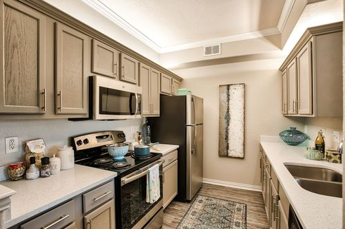 Ellery at Lake Sherwood - Kitchen featuring all stainless front appliances, large quartz counter tops, and tan cabinets.