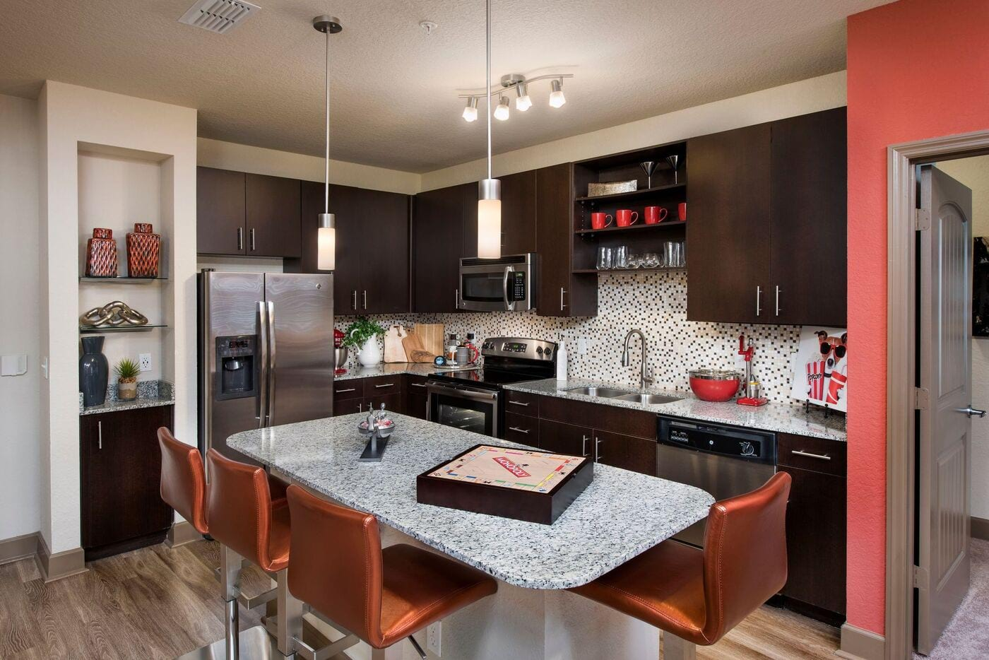 The Courtney at Universal Boulevard - Model kitchen with all stainless front appliances, large counter tops, island, and ebony cabinets.