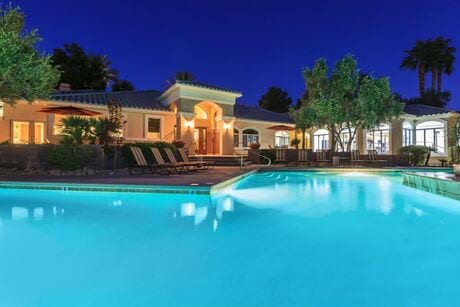Nighttime image of resort style pool with lounge chair seating.