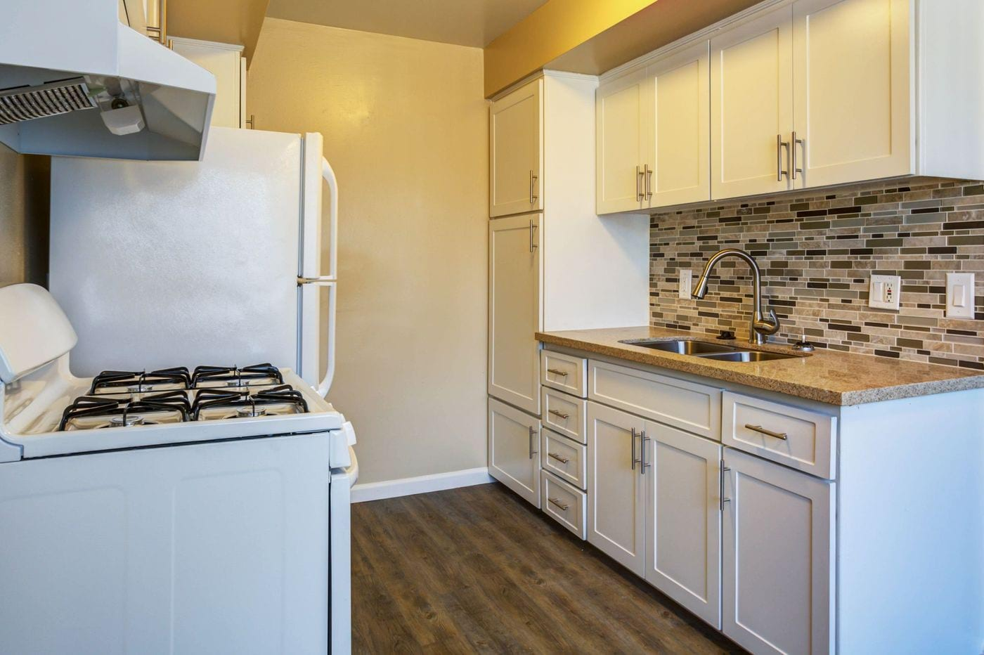 Kitchen with white cabinets and a ceramic tile backsplash.