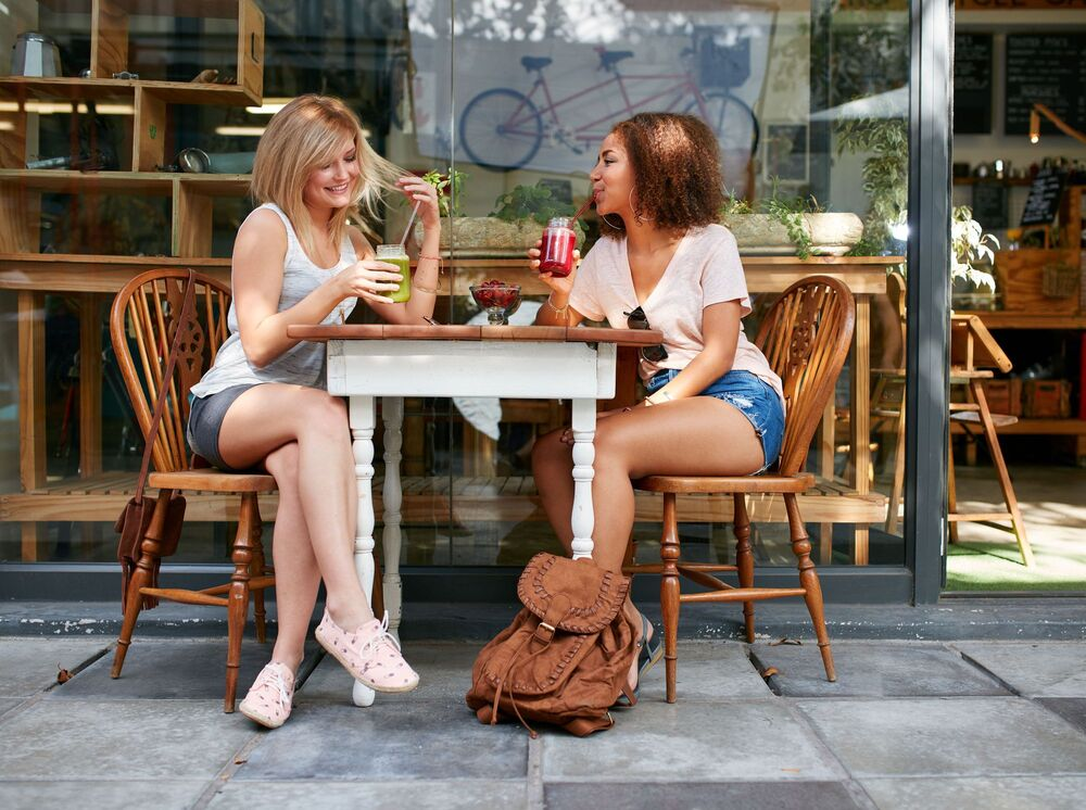 Audubon Village - Lifestyle filler image of two individuals enjoying smoothies at a table outside of a store front.