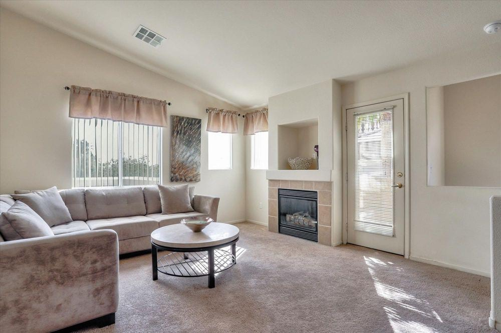 Spacious living room with plush carpeting and fireplace.
