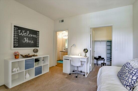 Image of model apartment bedroom with bed, desk, chair, and chalk board with storage underneath.