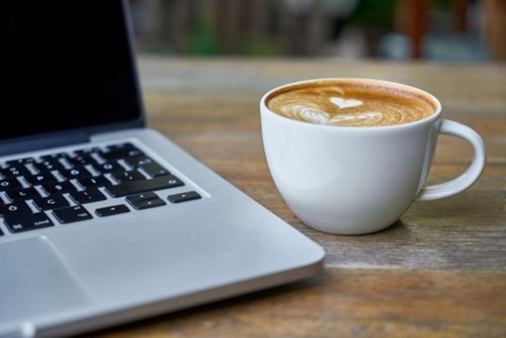 Stock image of laptop next to coffee cup.