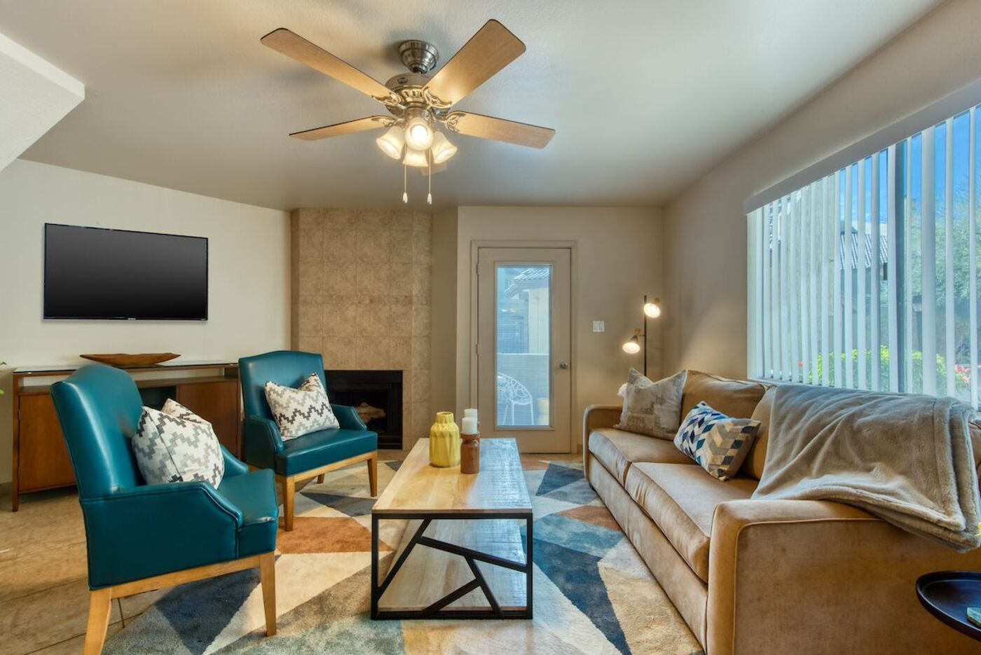 Tiled living room with ceiling fan, seating area, and view to kitchen and dining area.