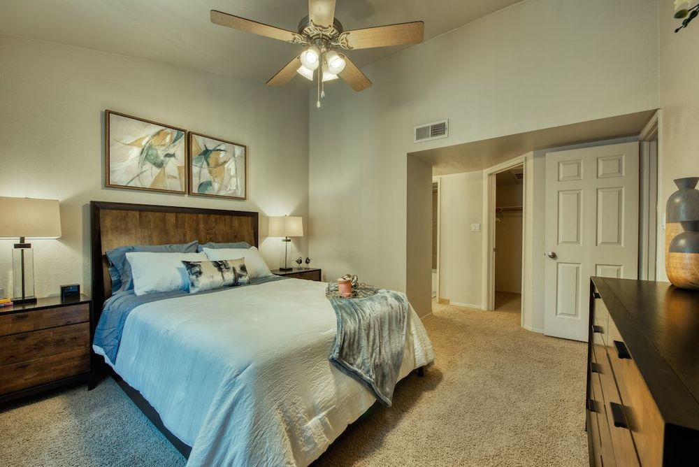Carpeted bedroom with ceiling fan, vaulted ceiling, walk-in closet and hallway to bathroom.