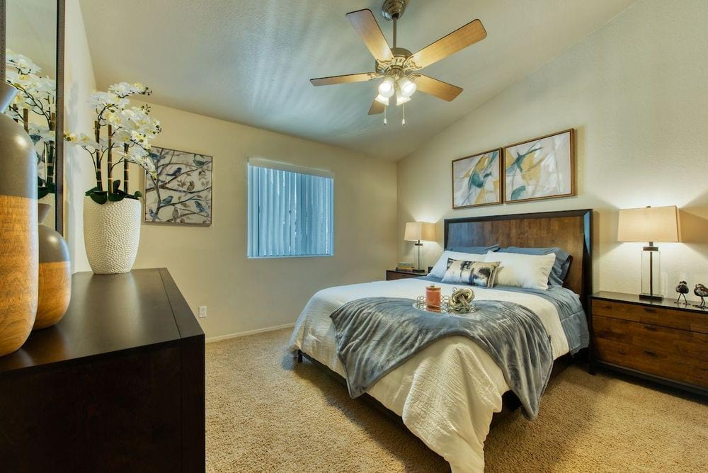 Carpeted bedroom with ceiling fan, small window, and vaulted ceiling.