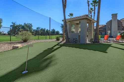 Golf putting green with gazebo and view of golf course.