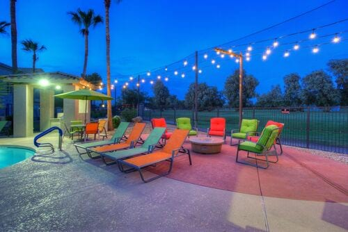 Evening view of pool area fire pit, gazebo, outdoor string lights and golf course view.