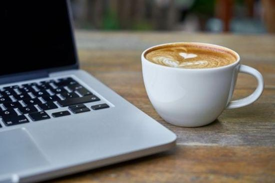 closeup photo of a laptop and coffee cup sitting on a table