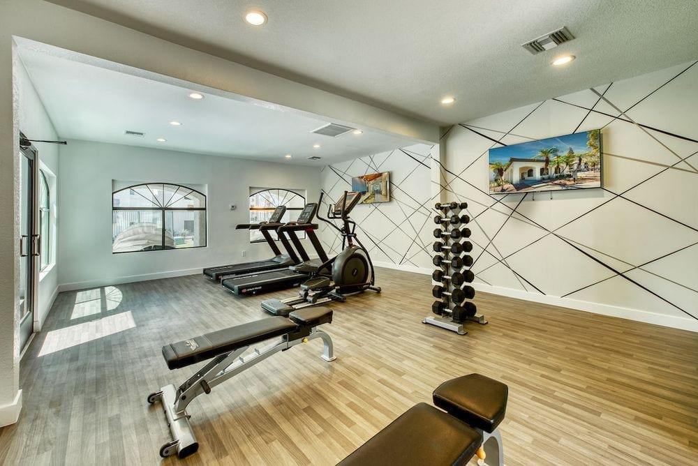 Vinyl floored fitness center with benches, free weights, cardio machines, and televisions.