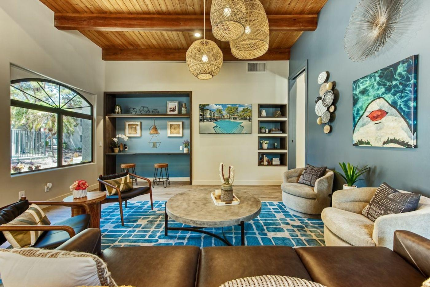 Modern resident clubhouse with couch, lounge chairs, television, and door to leasing desk.