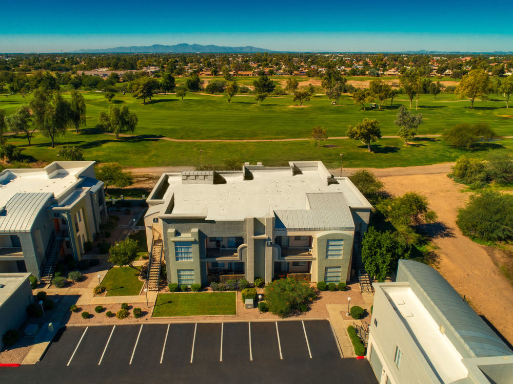 Aerial view of building exteriors and golf course.