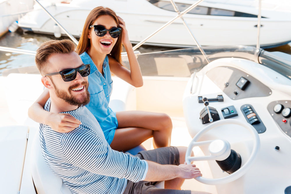 Image of man and women looking into camera smiling while sitting on a boat during a sunny day.