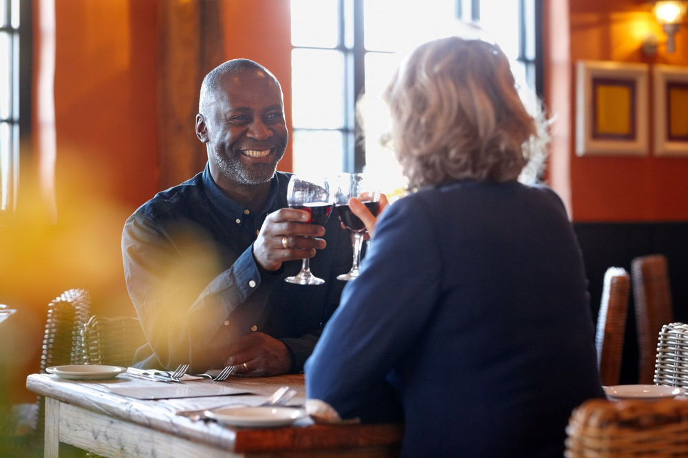 Image of man smiling at women, while clinking wine glasses in a restaurant setting.