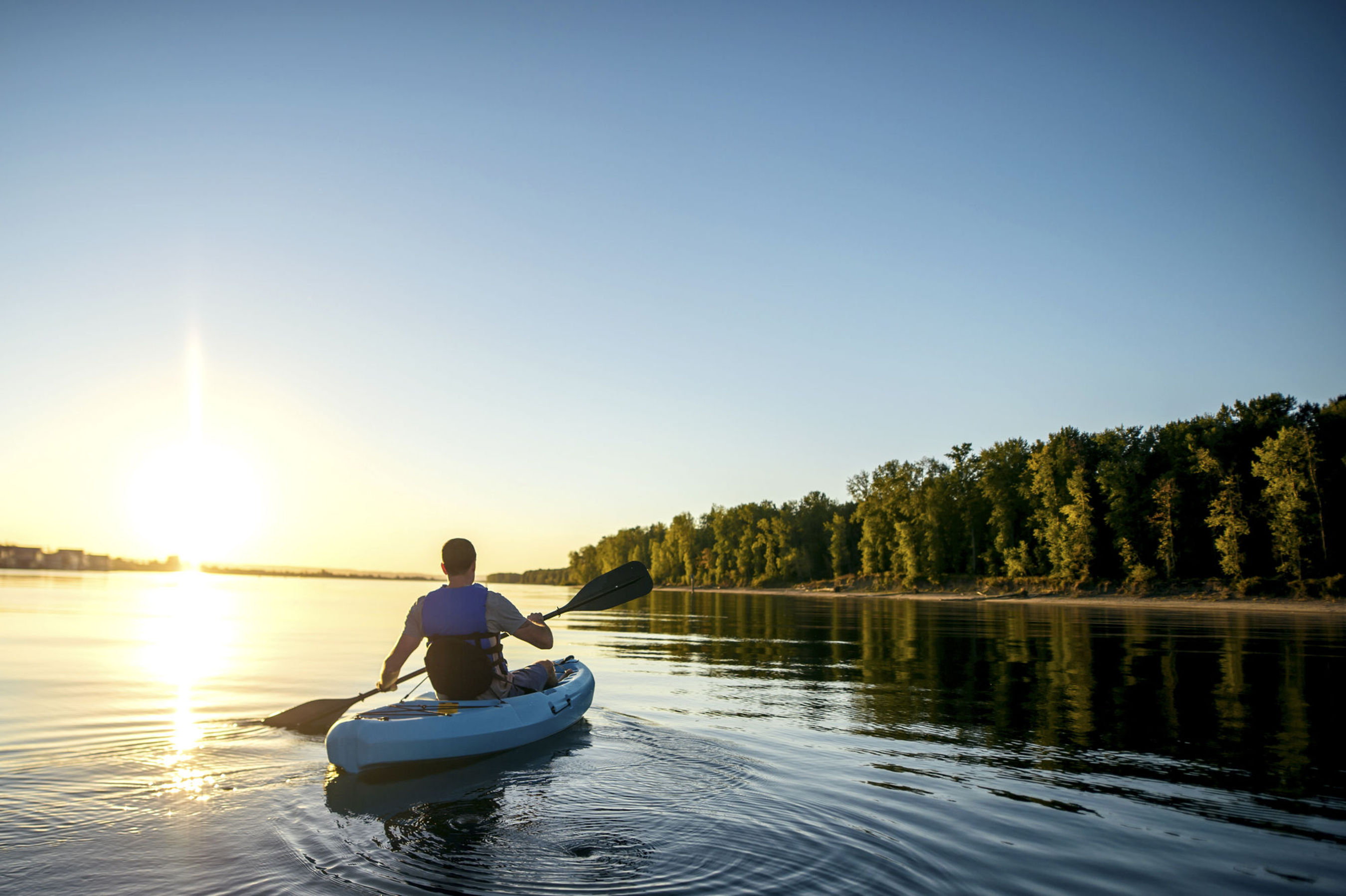 Image of man floating on water, sitting inside of a kayak and holding an oar.